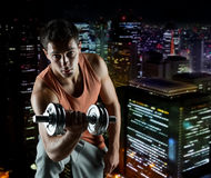 Young man with dumbbell flexing biceps. Sport, bodybuilding, training and people concept - young man with dumbbell flexing biceps over night city background Royalty Free Stock Photo