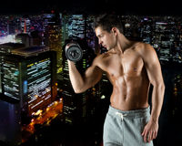 Young man with dumbbell flexing biceps. Sport, bodybuilding, training and people concept - young man with dumbbell flexing biceps over night city background Royalty Free Stock Photography