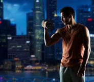 Young man with dumbbell flexing biceps. Sport, fitness, weightlifting, bodybuilding and people concept - young man with dumbbell flexing biceps over night city Royalty Free Stock Image