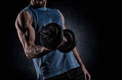Young man with dumbbell flexing muscles over gray background Royalty Free Stock Photography