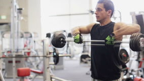 Young man with dumbbell in gym. Sport, bodybuilding, lifestyle and people concept - young man with dumbbell flexing muscles in gym stock video