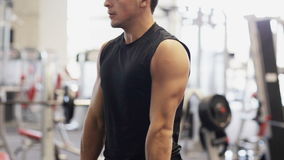 Young man with dumbbell in gym. Sport, bodybuilding, lifestyle and people concept - young man with dumbbell flexing muscles in gym stock footage