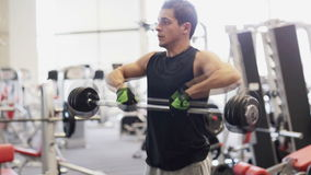 Young man with dumbbell in gym. Sport, bodybuilding, lifestyle and people concept - young man with dumbbell flexing muscles in gym stock video footage
