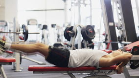 Young man with dumbbell in gym stock footage