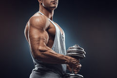 Young man with dumbbell prepare to flexing muscles over dark bac Royalty Free Stock Images