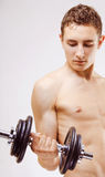 Young man with dumbbells Stock Image