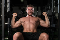 Young Man With Dumbbells Exercising Shoulders Royalty Free Stock Images