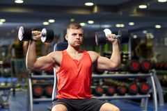 Young man with dumbbells flexing muscles in gym Stock Image