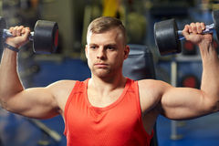 Young man with dumbbells flexing muscles in gym Royalty Free Stock Photography