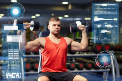 Young man with dumbbells flexing muscles in gym. Sport, fitness, bodybuilding and people concept - young man with dumbbells flexing muscles in gym over virtual Stock Photography
