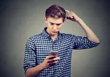 Young man dumbfounded about what he sees on cellphone, looking for solution stock photo