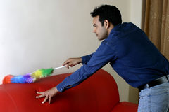 Young man dusting home Royalty Free Stock Image