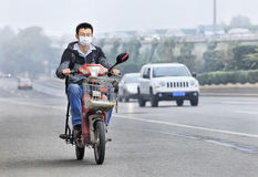 Young man on e-bike with a mouth cap against severe smog, Beijing, China Stock Image