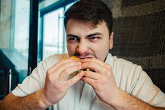 Young man eagerly eats burger. A young man in a white shirt eats greedily Burger Royalty Free Stock Image