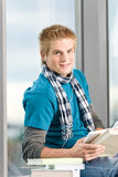 Young man with ear buds and books Stock Images