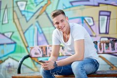 Cool young man with earphone and mobilephone Royalty Free Stock Images