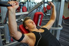 Young man with earphones exercising on gym machine Royalty Free Stock Photos