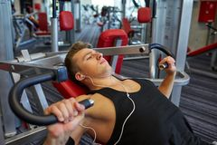 Young man with earphones exercising on gym machine Stock Image