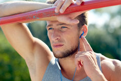 Young man with earphones and horizontal bar Royalty Free Stock Photos