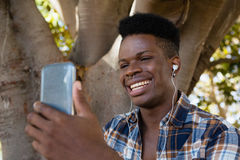 Young man with earphones listening to music on mobile phone Stock Photography