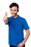 Young man with earphones and thumb up Stock Photography