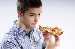 Young man eating. White, young, handsome man  eating pizza Royalty Free Stock Photo