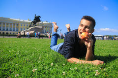 Young man eating an apple in Saint Petersburg, Russia Royalty Free Stock Photos