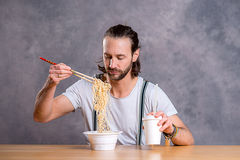 Young man eating asian food Stock Photos