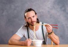 Young man eating asian food Stock Photos