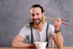 Young man eating asian food Stock Photo