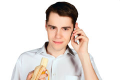 Young man eating banana and talking on the phone closeup Stock Photography