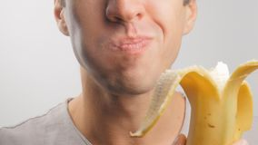 Close up of young man eating a banana on a white background. Young man eating a banana on a white background stock footage