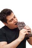 Young man eating big chocolate stock photography