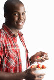 Young Man Eating Bowl Of Cereal In Studio Royalty Free Stock Photography
