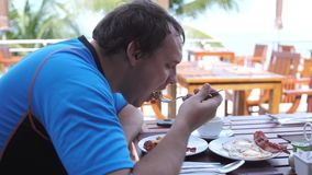Young man eating breakfast sitting in a beach cafe. slow motion. 3840x2160 stock video