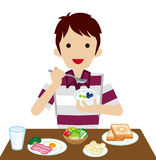 Young man eating breakfast Royalty Free Stock Photography