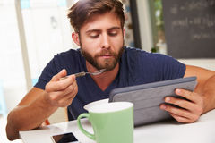 Young Man Eating Breakfast Whilst Using Digital Tablet Royalty Free Stock Images