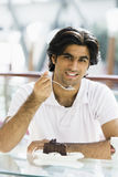 Young man eating cake in cafe. Man eating piece of chocolate cake in cafe Royalty Free Stock Images