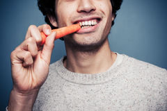 Young man eating a carrot Royalty Free Stock Images