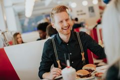 Young man eating cheeseburger in diner Stock Photo