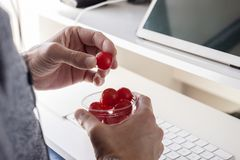 Young man eating cherry tomatoes at the office royalty free stock photo