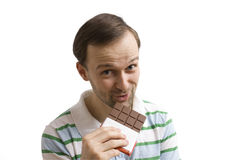 Young man eating chocolate. Young man being happy to eat a chocolate Royalty Free Stock Images