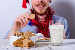 Young man eating christman gingerbread cookies Stock Photography