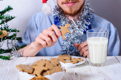 Young man eating christman gingerbread cookies Stock Photo