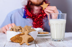 Young man eating christman gingerbread cookies Stock Images