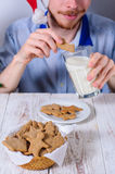 Young man eating christman gingerbread cookies Royalty Free Stock Photo