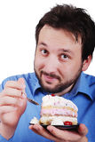 Young man eating colorful cake isolated Royalty Free Stock Images