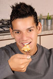 Young man eating cornflakes. Young hispanic man eating cornflakes for breakfast. Selective focus Royalty Free Stock Photos