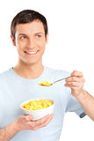 A young man eating cornflakes. Isolated on white background Stock Photos