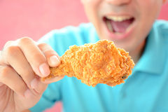 Young man eating deep fried chicken leg or drumstick Royalty Free Stock Photography